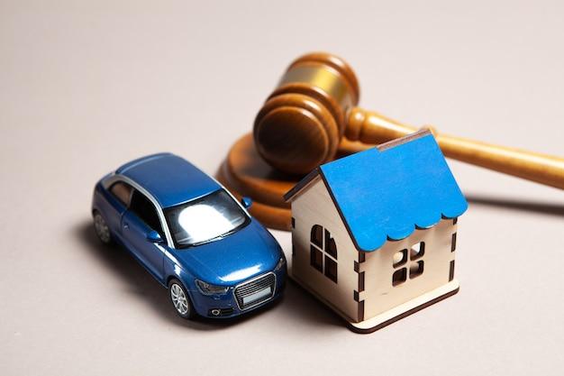 탁자 위에는 망치, 집과 차가 있습니다. 재산 소송 개념