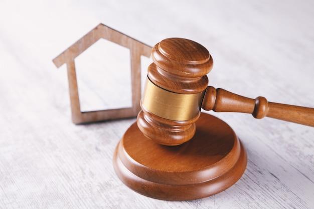탁자 위에는 판사의 망치와 집이 있습니다. 소송