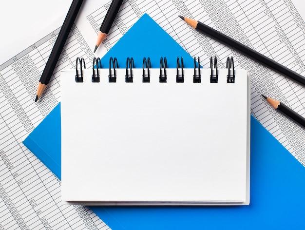 テーブルには、レポート、青いノート、黒い鉛筆、テキストを挿入する場所のあるノートがあります。テンプレート。ビジネスコンセプト