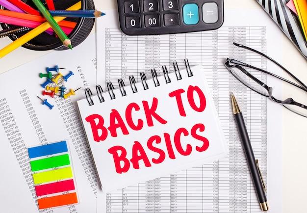テーブルには、レポート、電卓、色鉛筆とステッカー、ペン、「基本に戻る」というテキストが書かれたノートがあります。
