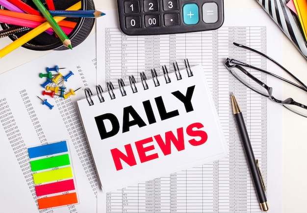 テーブルには、レポート、電卓、色鉛筆とステッカー、ペン、dailynewsというテキストのノートがあります。