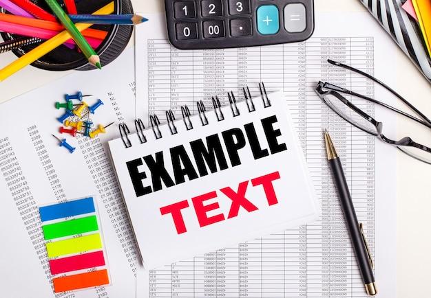 На столе отчеты, калькулятор, цветные карандаши и наклейки, ручка и блокнот с текстом. пример текст.