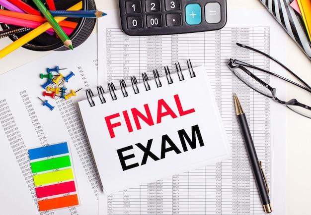 テーブルには、レポート、電卓、色鉛筆とステッカー、ペン、テキストがfinalexamのノートがあります。