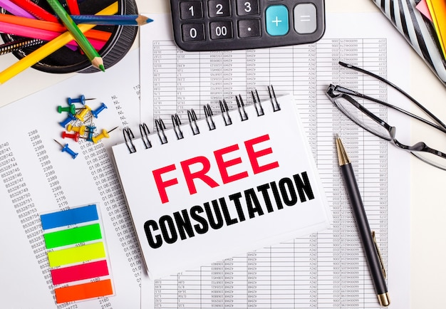 На столе отчеты, калькулятор, цветные карандаши и наклейки, ручка и блокнот с текстом бесплатная консультация.