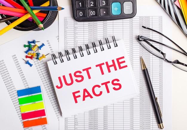 На столе отчеты, калькулятор, цветные карандаши и наклейки, ручка и блокнот с текстом просто факты.