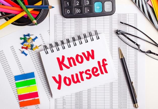 테이블에는 보고서, 계산기, 색연필 및 스티커, 펜 및 노트북에 know yourself라는 텍스트가 있습니다.