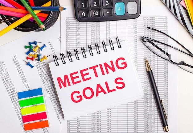 На столе отчеты, калькулятор, цветные карандаши и наклейки, ручка и блокнот с текстом встречи целей.