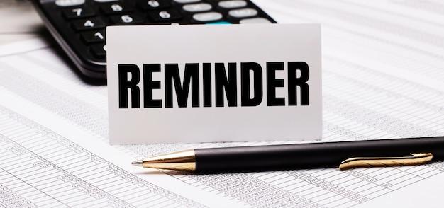 テーブルには、レポート、ペン、電卓、reminderというテキストの白いカードがあります。