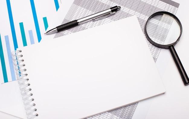 テーブルには、レポート、チャート、ペン、虫眼鏡、テキストを挿入する場所のある白い空白のノートがあります。レンプレート。ビジネスコンセプト