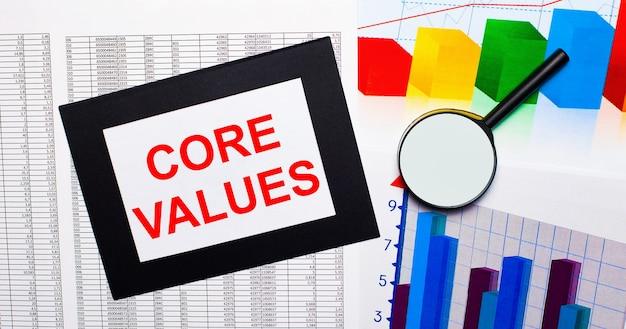 На столе отчеты разноцветные диаграммы, лупа и лист бумаги в черной рамке с текстом основные значения. бизнес-концепция