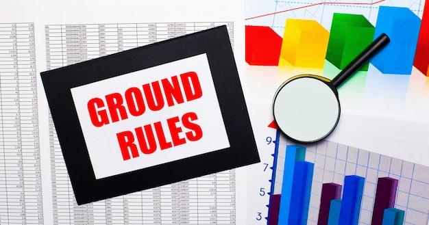 テーブルには、マルチカラーのチャート、虫眼鏡、黒いフレームの紙に「groundrules」というテキストが記載されたレポートがあります。