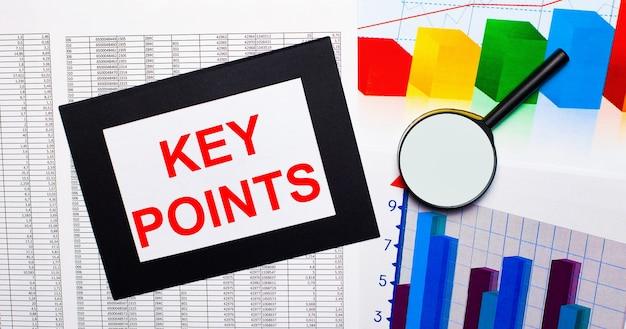 テーブルには、マルチカラーのチャート、虫眼鏡、黒いフレームの紙にkeypointsというテキストが記載されたレポートがあります。ビジネスコンセプト