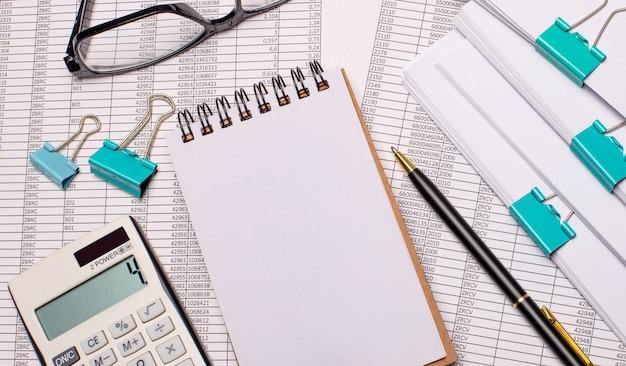 テーブルの上には、テキスト、ペン、メガネ、レポートを挿入する場所のある空白のノートブックがあります