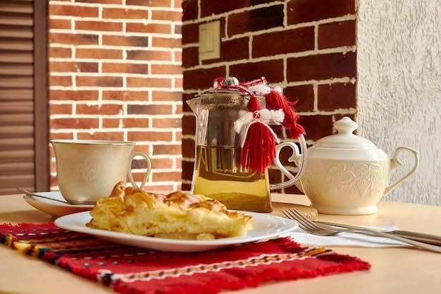 テーブルの上には、オムレツ、フォーク、ナイフ、お茶の入ったティーポット、シュガーボウル、カップ、皿に受け皿があります。