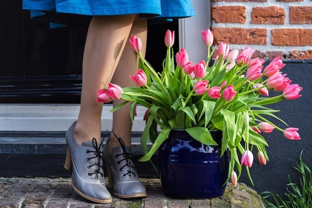 家の敷居には、ピンクのチューリップとかかとに女性の脚が付いた花瓶があります。オランダ