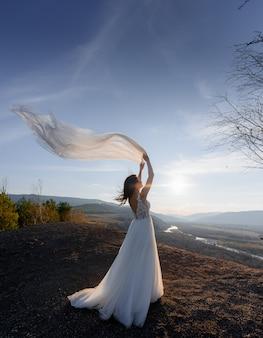 夕方の丘の上に、波状のベールを持つ花嫁の背面図