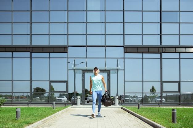 途中。メガポリスの空港、モダンなガラス張りの建物に向かって歩いているスポーツマン。競技への飛行前