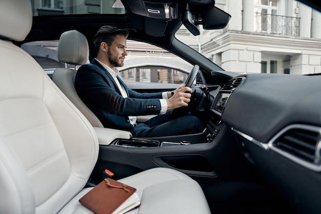 비즈니스 미팅 가는 길. 차를 운전하는 동안 똑바로 찾고 전체 양복에 잘 생긴 젊은 남자