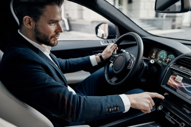 비즈니스 미팅 가는 길. 차를 운전하는 동안 버튼을 누르는 전체 양복에 잘 생긴 젊은 남자