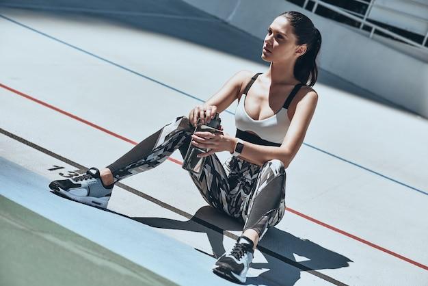 На пути к отличной форме. привлекательная молодая женщина в спортивной одежде отдыхает и смотрит в сторону