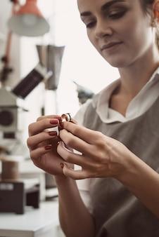 На пути к совершенству. вертикальное фото женщины-ювелира, исследующей серебряное кольцо в мастерской. ювелир женщина осматривает ювелирные изделия.