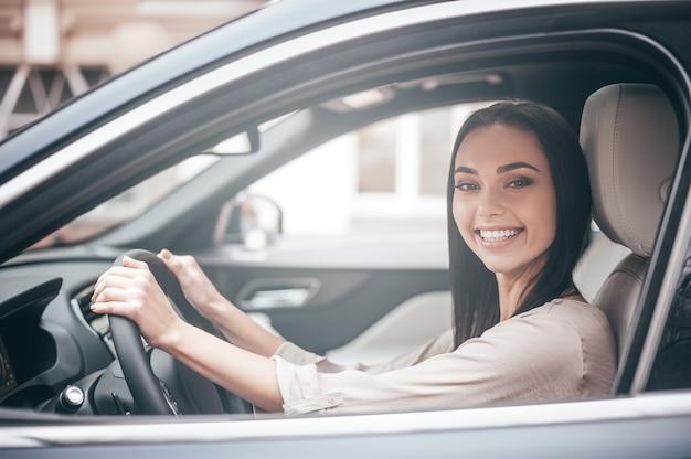 성공의 길에. 앞좌석에 앉아 차를 운전하는 동안 웃고 있는 자신감 있는 젊은 여성