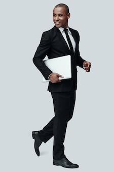 성공의 길에. 회색 배경에 서서 노트북을 들고 웃고 있는 정장 차림의 잘생긴 젊은 아프리카 남자의 전체 길이