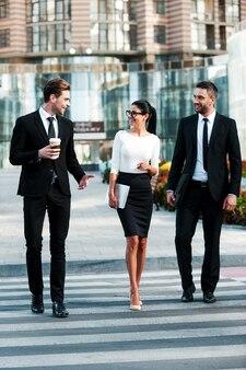 成功への道。お互いに話している3人の笑顔のビジネスマンの全長