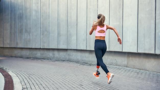 快適な義足を持つ若い障害のある女性のサクセスバックビューへの道