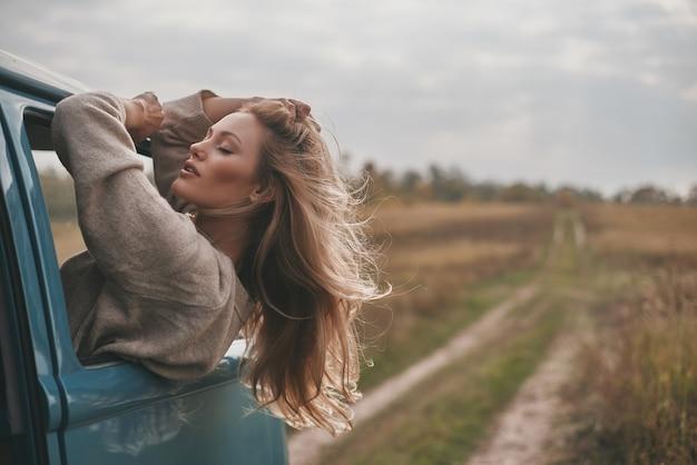알려지지 않은 장소로가는 중. 매력적인 젊은 여자가 밴 창 밖으로 기울고 차 여행을 즐기면서 머리에 손을 유지
