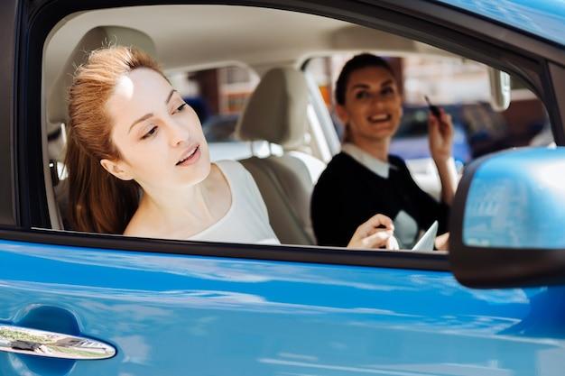 На пути на работу. привлекательная приятная милая бизнесвумен сидит в машине со своим коллегой и смотрит в окно, глядя на вид Premium Фотографии