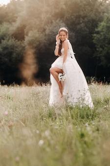 В день свадьбы элегантная невеста в белом длинном платье и перчатках с букетом в руках стоит на поляне, наслаждаясь природой. беларусь.