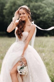 결혼식 날, 하얀 긴 드레스를 입은 우아한 신부와 손에 꽃다발을 든 장갑은 자연을 즐기는 개간에 서 있습니다. 벨라루스.