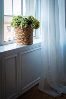 窓には薄緑色のアジサイが入った籐のかごがあります