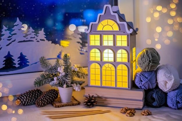 창턱, 실 타래 사이에서 오래된 유럽 집 형태의 야간 조명이 빛납니다.