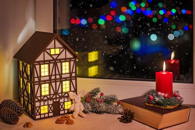 На подоконнике среди елочных игрушек ночник в виде фахверкового домика, горит красная свеча.