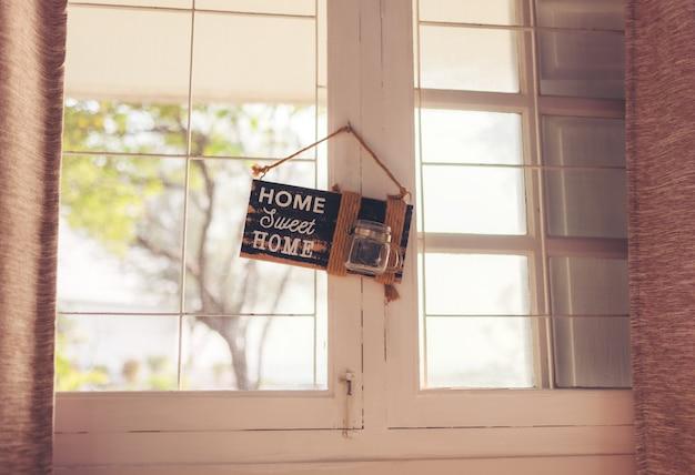 На деревянной двери есть приветственный коврик с надписью «дом, милый дом».