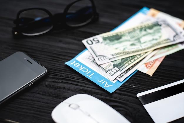 나무로 된 검은 탁자에는 신용카드와 안경, 여행 및 여행사 개념의 티켓이 있습니다.