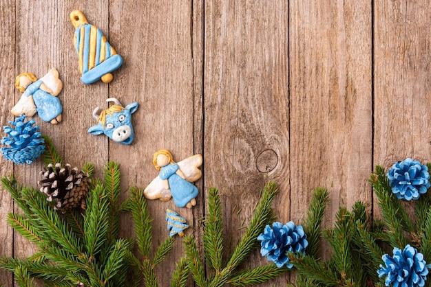 На деревянном столе лежат еловые ветки с небольшими рождественскими сувенирами.