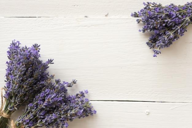 木製のテーブルには、植物標本用のラベンダーの花の紫色の花束があります。フラットレイ