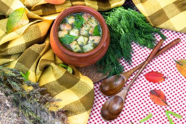 木製のテーブルの上には、おいしいスープが入った土鍋があります。