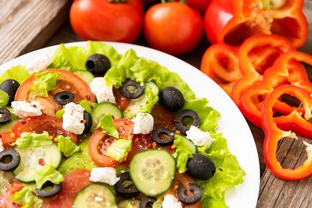 木製のテーブルにはギリシャ風サラダとフェタチーズのプレートがあります。