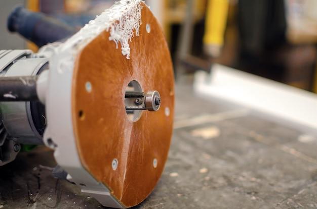作業台の上には、削りくずの中にカッターを備えた手動フライス盤があります。家具の生産コンセプト。