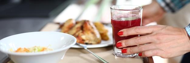 На подносе тарелки с обеденной посудой, женская рука держит стакан красной жидкости