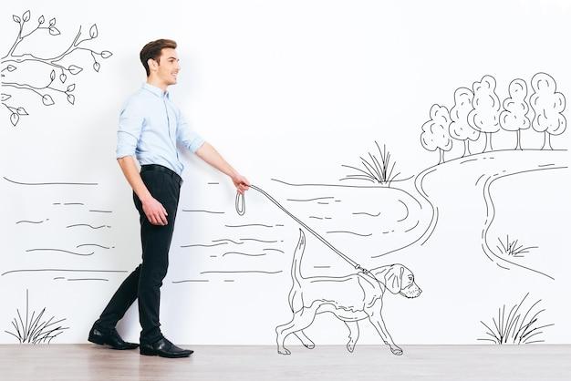 그의 강아지와 함께 산책에. 공원의 그림에서 자신의 그려진 개를 산책하는 잘 생긴 젊은 남자