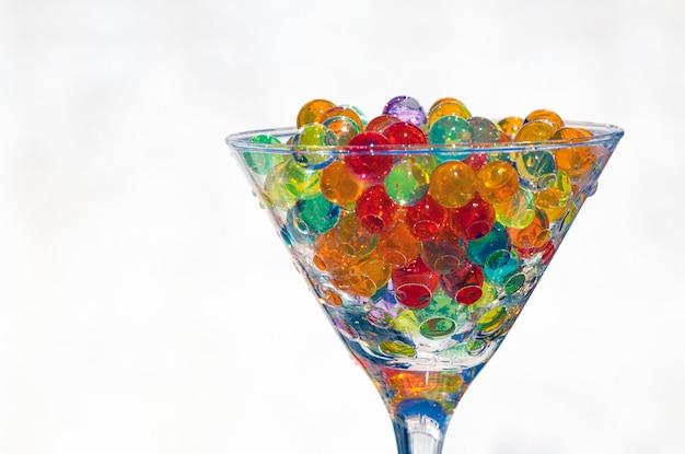 На белом фоне и солнечном свете стеклянная чашка, полная полупрозрачных разноцветных бусинок, выборочный фокус и художественное размытие.
