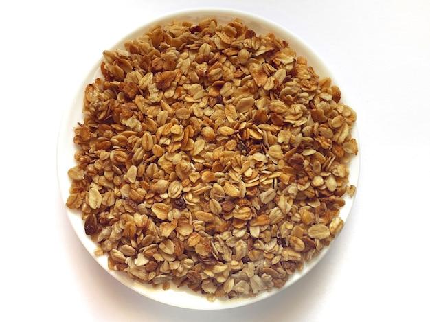 На белом изолированном фоне мюсли на тарелке блюдо для завтрака закуска на фото гранулы о