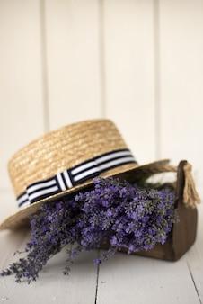 白の上にオリーブラベンダーの香りのよい新鮮な花束が付いている木製のバスケットがあり、その上に魅力的な帽子があります。
