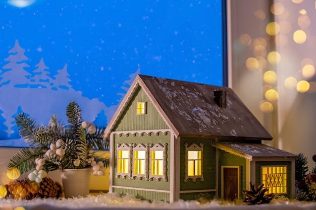 クリスマスツリーの装飾の間の窓辺に村の家の形で夜の光が輝きます