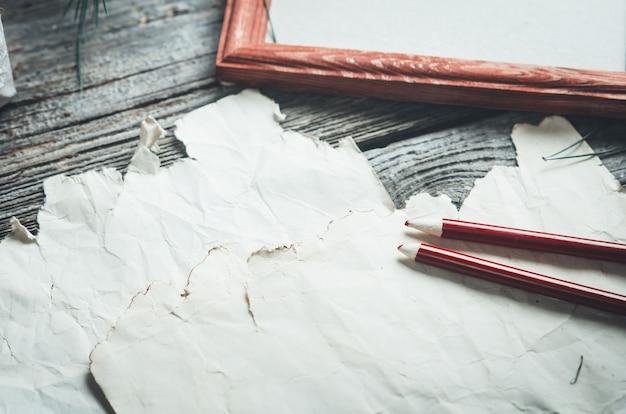 木製の古いテーブルに古いシート、鉛筆の横に羊皮紙がきれいに配置されています